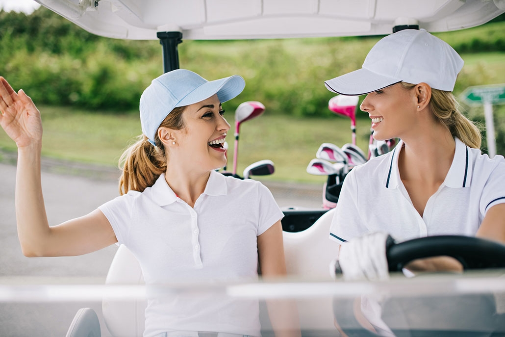 portrait of cheerful female golfers in caps riding golf cart at golf course